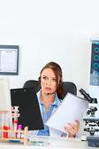 Doctor mujer se confunde con auriculares en portapapeles y nota — Foto de Stock