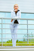 Portrait of smiling business woman leaning on railing at office building — Stock Photo