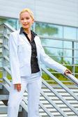Usmívající se obchodní žena stojící na schodech v kanceláři budovy a držení h — Stock fotografie