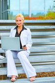 Happy business woman sitting on stairs at office building and wo — Stock Photo