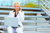Smiling business woman sitting on stairs talking on mobile and l — Stock Photo
