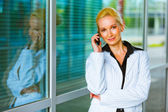 Smiling business woman talking on mobile at office building — Stock Photo