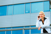 Business woman leaning on railing at office building and talking — Stock Photo