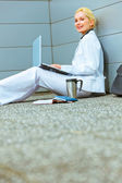 Smiling modern business woman on floor at office building working on laptop — Stock Photo