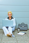 Concentrated business woman sitting on floor at office building — Stock Photo