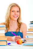 Cheerful teen girl sitting at table with lots of books — Stock Photo