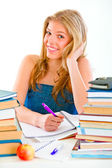 Smiling teen girl sitting at table with lots of books — Stock Photo