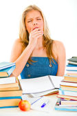 Yawning tired teengirl sitting at table with piles of books — Stock Photo