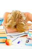 Tired teen girl sleeping at table with piles of books — Stock Photo