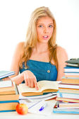 Curious girl sitting at table and pointing in book — Stock Photo