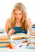 Adolescente sentado à mesa e lendo o livro a estudar — Fotografia Stock