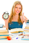 Smiling teengirl with alarm clock sitting at table — Stock Photo