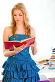 Pretty girl standing near table and reading book — Stock Photo