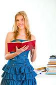 Smiling girl standing near desk with open book — Stock Photo