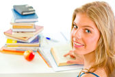 Smiling teengirl sitting at table with books — Stock Photo