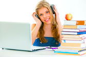 Sitting at table smiling teengirl with headphone listening audio lessons — Stock Photo