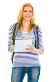 Smiling teengirl with schoolbag writing in notebook — Stock Photo