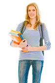 Smiling young girl with schoolbag holding schoolbooks in hands — Stock Photo
