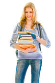 Smiling teen girl with pile of schoolbooks in hands reading — Stock Photo