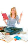 Pensive teenager sitting on floor among schoolbooks and studying — Stock Photo