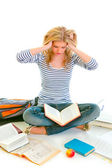 Teen girl sitting on floor among schoolbooks and studying hard — Stock Photo
