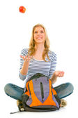 Smiling teengirl sitting on floor with schoolbag and throwing apple up — Stock Photo