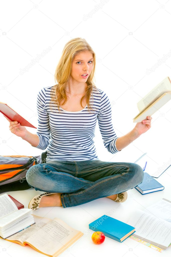 Shocked teen girl sitting on floor with books and  preparing for exams isolated on white — Stock Photo #8638878