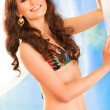 Smiling pretty girl in bikini posing in summerhouse on beach — Stock Photo #8640223