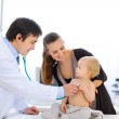 Surprised baby being checked by a doctor using a stethoscope — Stock Photo