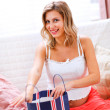 Smiling pregnant woman sitting on couch and opening shopping bag - Stock Photo