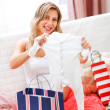 Smiling pregnant sitting on couch with shopping bags and examine — Stok fotoğraf