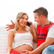 Young pregnant woman sitting with husband on couch and speaking — Stock Photo