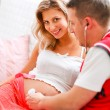Young man listening baby in his pregnant wifes tummy using stethoscope — Stock Photo