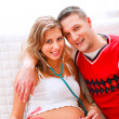 Smiling pregnant woman sitting on sofa with young husband — Stock Photo