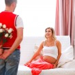 Husband hiding flowers from his excited pregnant wife — Stock Photo #8643661