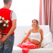 Husband hiding flowers from his excited pregnant wife - Stock Photo
