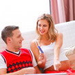 Happy young pregnant woman showing her husband what she likes to buy online — Stock Photo