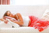 Lovely pregnant woman sleeping on sofa — Stok fotoğraf