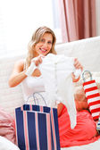 Smiling pregnant sitting on couch with shopping bags and examine — Stock Photo