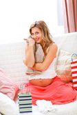 Happy pregnant woman sitting on sofa with shopping bags — Stock Photo