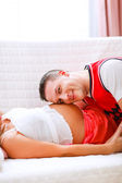 Closeup on young husband listening his pregnant wifes tummy — Stock fotografie