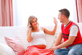 Pregnant woman interrupting her husband to answer phone call — Stock Photo