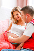 Young man listening baby in his pregnant wifes tummy using stethoscope — Stockfoto
