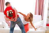 Husband hiding flowers from his curious pregnant wife — Stock Photo