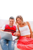 Happy young man showing his pregnant wife something in laptop — Stock Photo