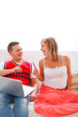 Happy young pregnant woman with husband shopping on Internet — Stock Photo