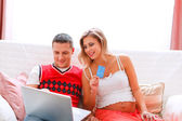 Happy young pregnant woman with husband making on-line purchases — Stock Photo