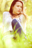 Thoughtful pretty girl sitting on green grass — Stock Photo