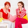 Two surprised girlfriends sitting on sofa — Stock Photo #8651321