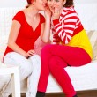 Stockfoto: Pretty girl whispering gossips in ear of her interested girlfrie